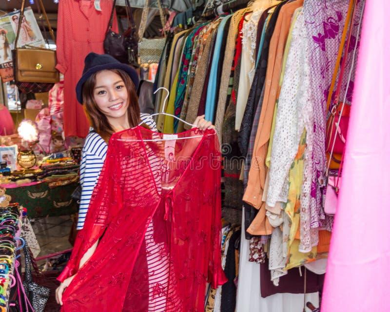 Femme asiatique regardant des vêtements sur le support images stock