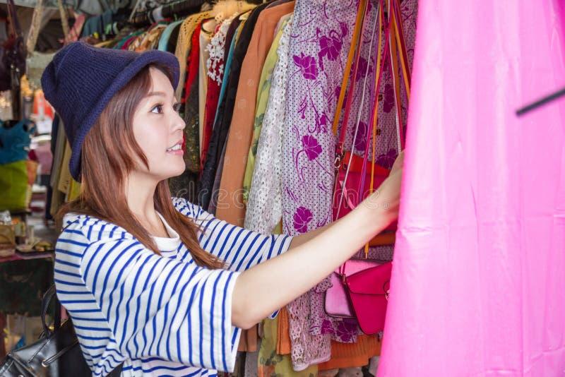 Femme asiatique regardant des vêtements sur le support photographie stock