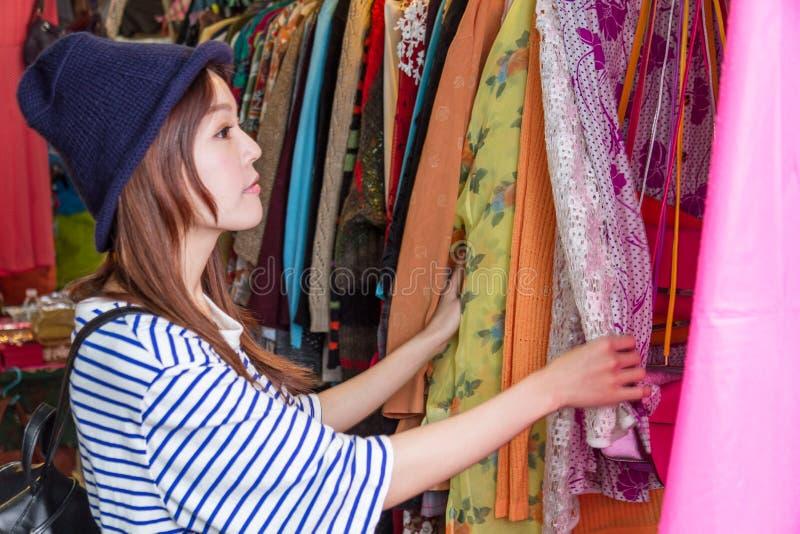 Femme asiatique regardant des vêtements sur le support photo libre de droits