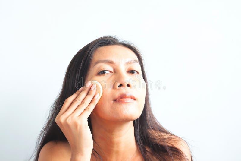 Femme asiatique regardant la caméra et appliquant la poudre de base sur son visage beaut? images libres de droits