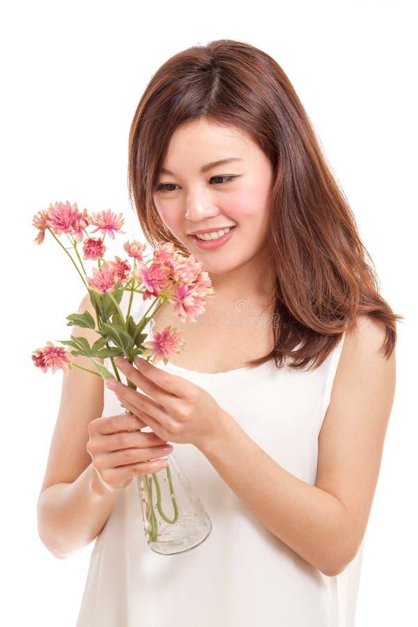 Femme asiatique regardant les fleurs roses photographie stock libre de droits