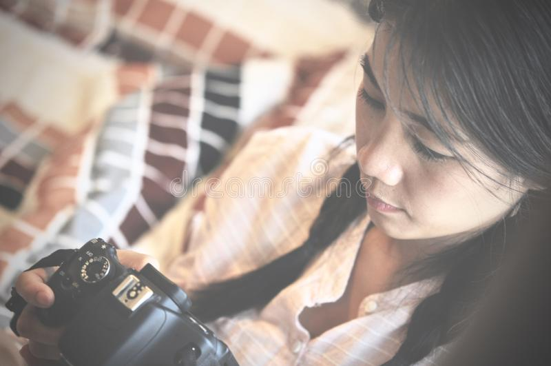 Femme asiatique regardant ses photos sur son appareil-photo, tout en se reposant près de la fenêtre photos libres de droits