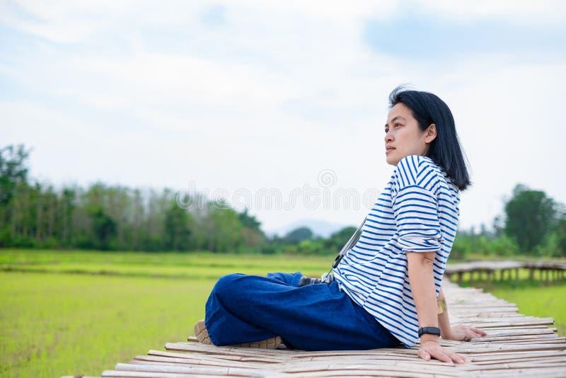 Femme asiatique reposant la jambe croisée sur le pont en bambou au gisement de riz à photographie stock
