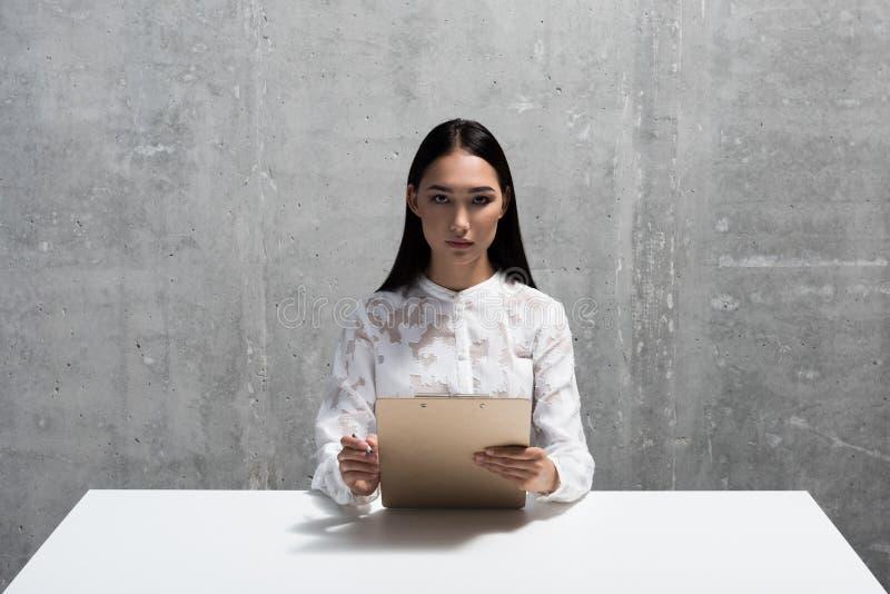 Femme asiatique sévère interviewant quelqu'un photo stock