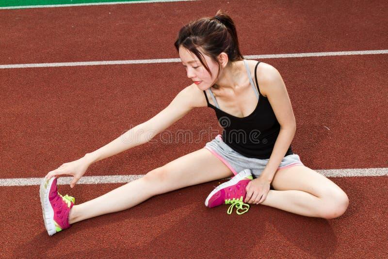 Femme asiatique s'étirant sur la voie photos stock