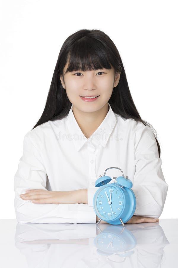 Femme asiatique s'asseyant au bureau souriant avec l'horloge sur le backgro blanc images stock