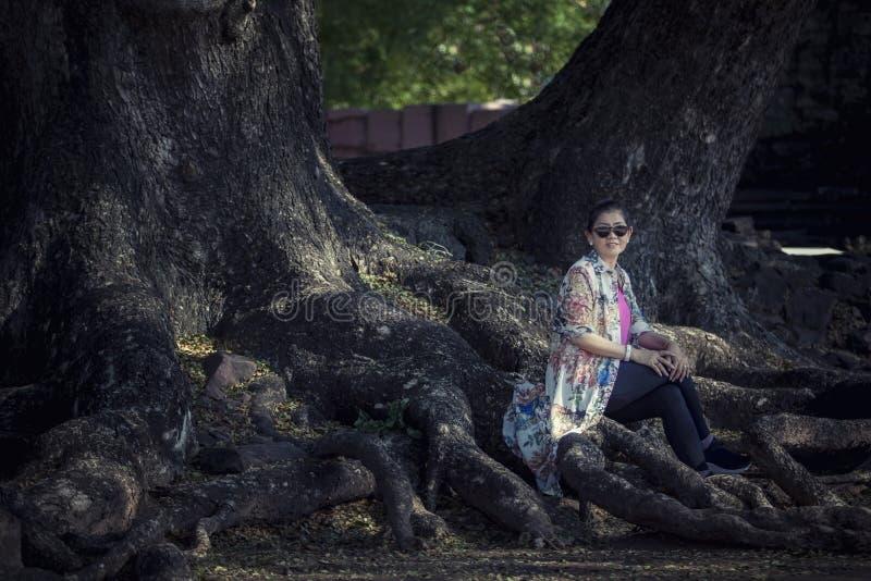 Femme asiatique s'asseyant sur la grande racine d'arbre de pluie dans le destinati de déplacement photo libre de droits