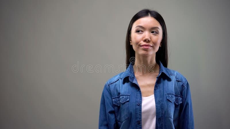 Femme asiatique satisfaite pensant aux vacances, rêvant des moments de plaisir images libres de droits