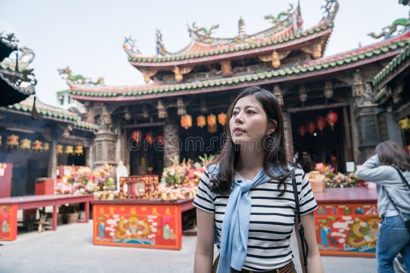 Femme asiatique se tenant et regardant autour dans le temple photographie stock libre de droits