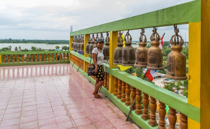 Femme asiatique se tenant nu-pieds devant la rangée des cloches photo stock