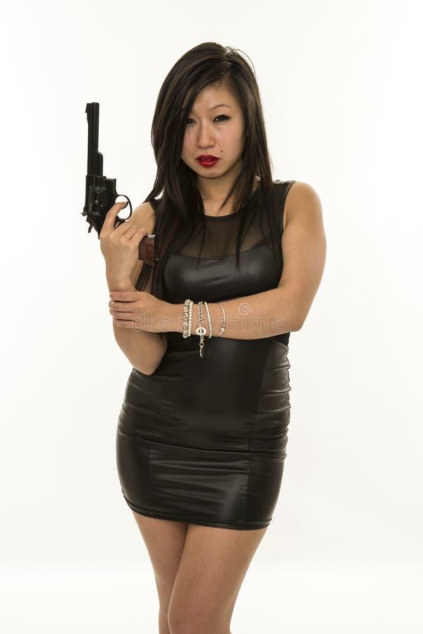 Femme asiatique sexy avec la robe serrée noire et revolver image libre de droits