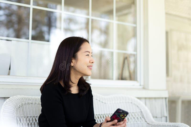 Femme asiatique souriant avec la main tenant le téléphone portable se reposant sur la chaise de balcon images libres de droits