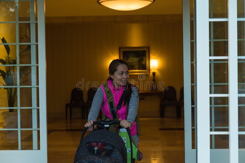 Femme asiatique souriant et poussant la voiture d'enfant image stock
