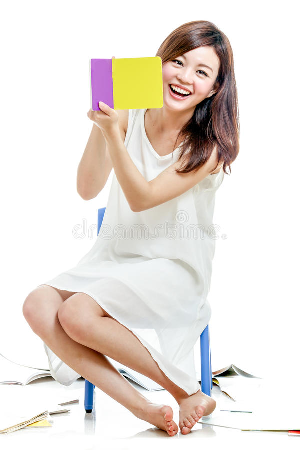 Femme asiatique souriant un livre coloré de support photos stock