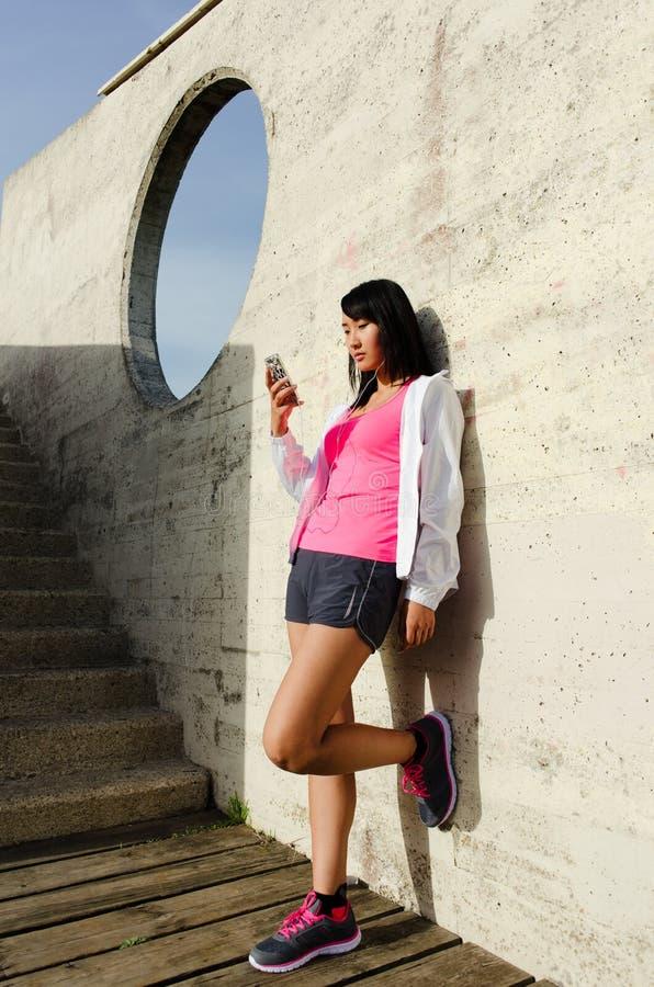 Femme asiatique sportive prenant un repos de séance d'entraînement avec le smartphone images libres de droits
