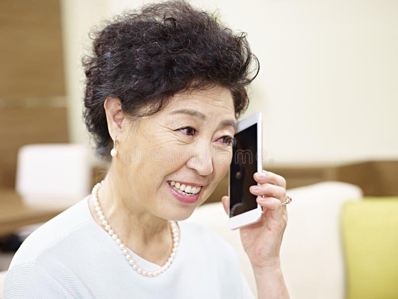 Femme asiatique supérieure parlant sur le téléphone portable photos stock