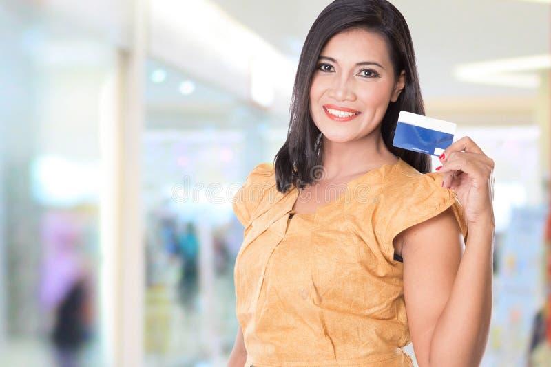Femme asiatique supportant la carte de crédit, le montrant à l'appareil-photo photo stock