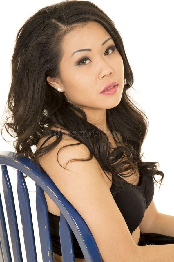 Femme asiatique sur un regard étroit de chaise bleue image stock