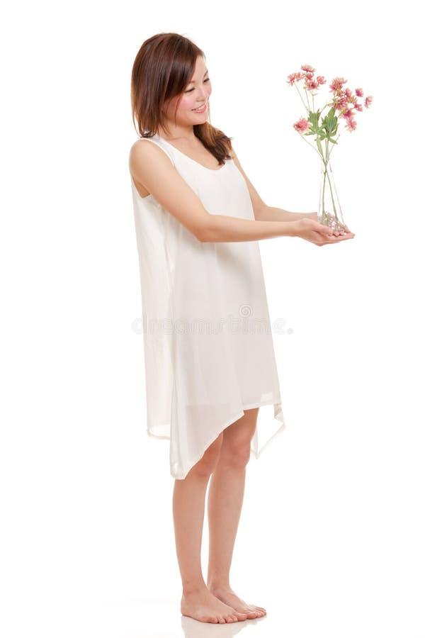 Femme asiatique tenant des fleurs dans un vase photos stock