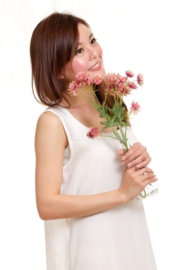 Femme asiatique tenant des fleurs dans un vase images libres de droits