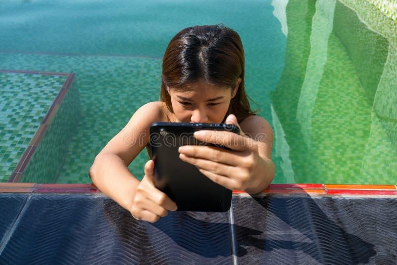 Femme asiatique tenant le comprimé dans l'espace piscine de natation image libre de droits