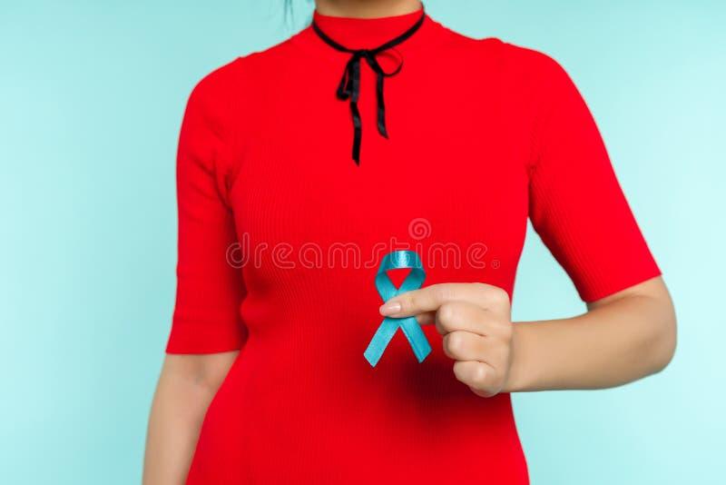Femme asiatique tenant un ruban bleu dans sa main Problème et cancer de la prostate de mauvais traitement à enfant de symbole photos stock