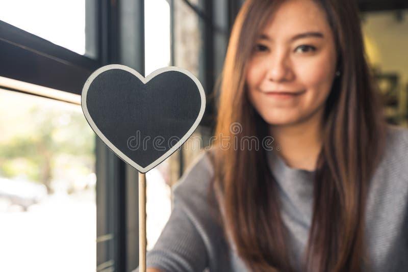 Femme asiatique tenant un signe vide de tableau noir de forme de coeur avec se sentir heureux et dans l'amour photographie stock libre de droits