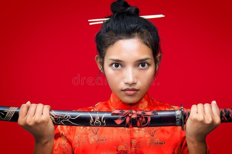 Femme asiatique tenant une épée images stock