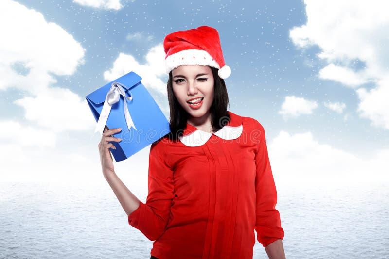 Femme asiatique utilisant le chapeau de Santa tenant le cadeau image libre de droits