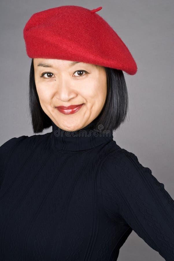Femme asiatique utilisant un béret rouge image libre de droits