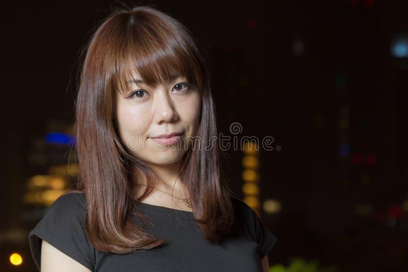 Femme assez asiatique avec la lumière de ville derrière elle image libre de droits