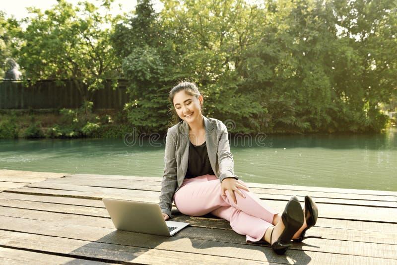 Femme assez asiatique d'affaires travaillant avec son ordinateur portable photo libre de droits
