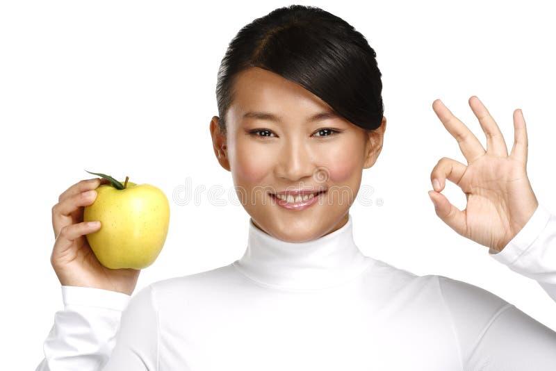 Femme assez asiatique de jeunes mangeant une pomme photo libre de droits