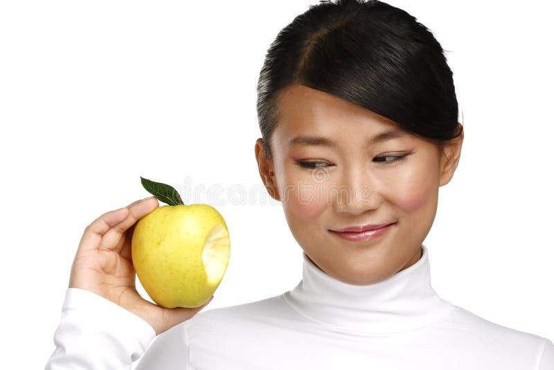 Femme assez asiatique de jeunes mangeant une pomme photo stock