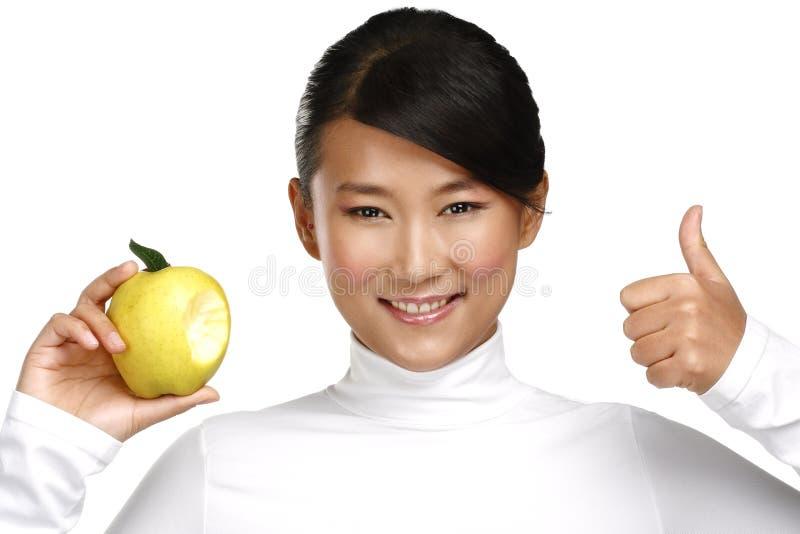 Femme assez asiatique de jeunes mangeant une pomme photos libres de droits