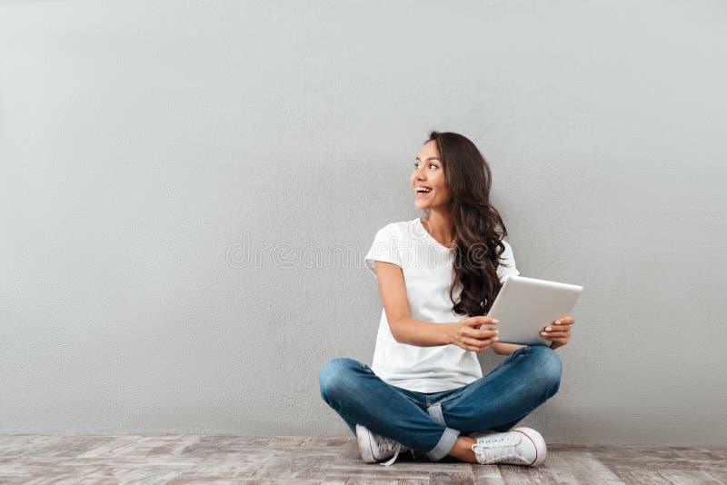 Femme assez asiatique heureuse tenant la tablette photos libres de droits