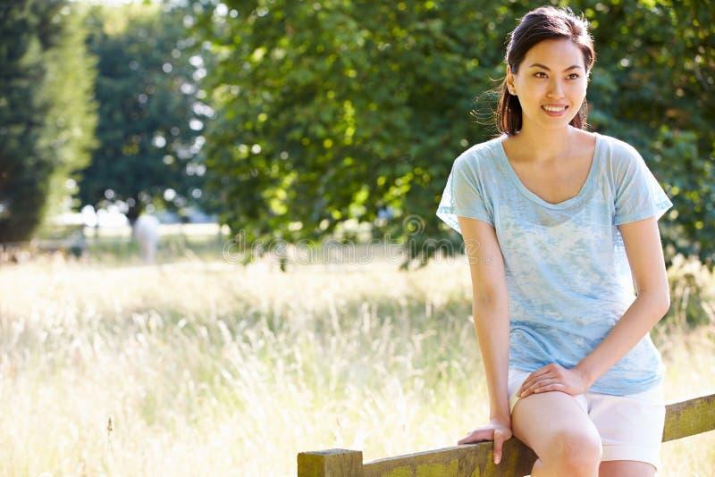 Femme assez asiatique s'asseyant sur la barrière In Countryside image libre de droits