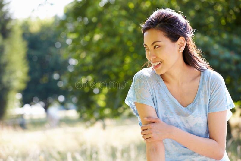 Femme assez asiatique s'asseyant sur la barrière In Countryside photographie stock libre de droits