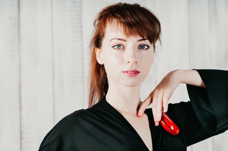 Femme assez aux yeux bleus dans la robe noire, avec les castagnettes rouges, lumière images libres de droits
