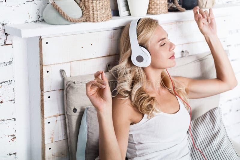 Femme assez blonde écoutant la musique à la maison photos stock