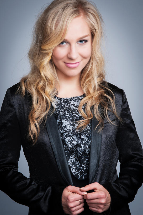Femme assez blonde dans la veste noire image libre de droits