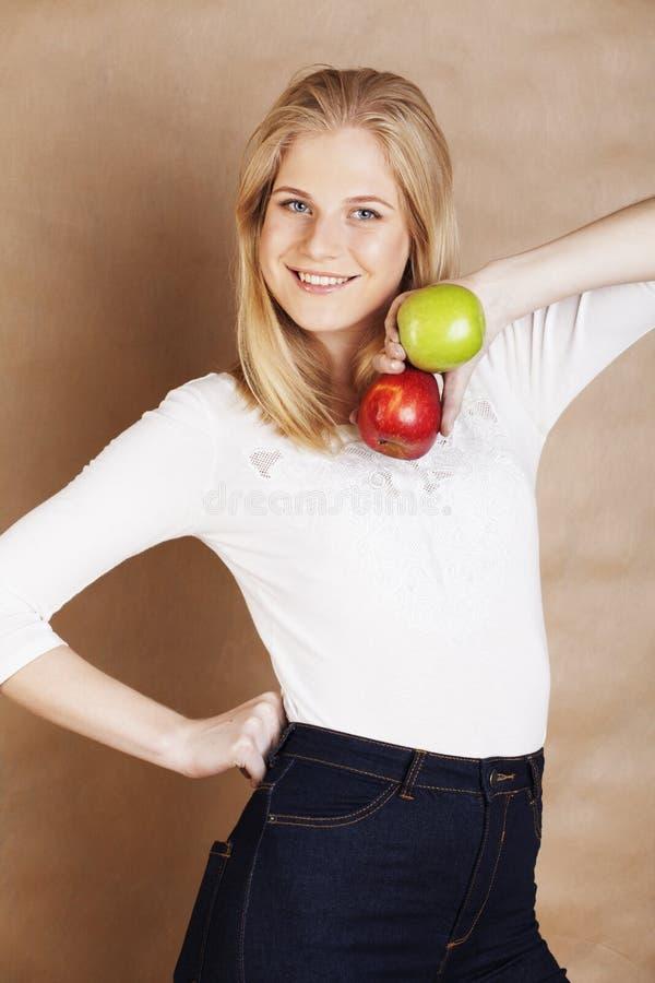 Femme assez blonde de jeunes choisissant entre le SM rouge et vert de pomme image stock