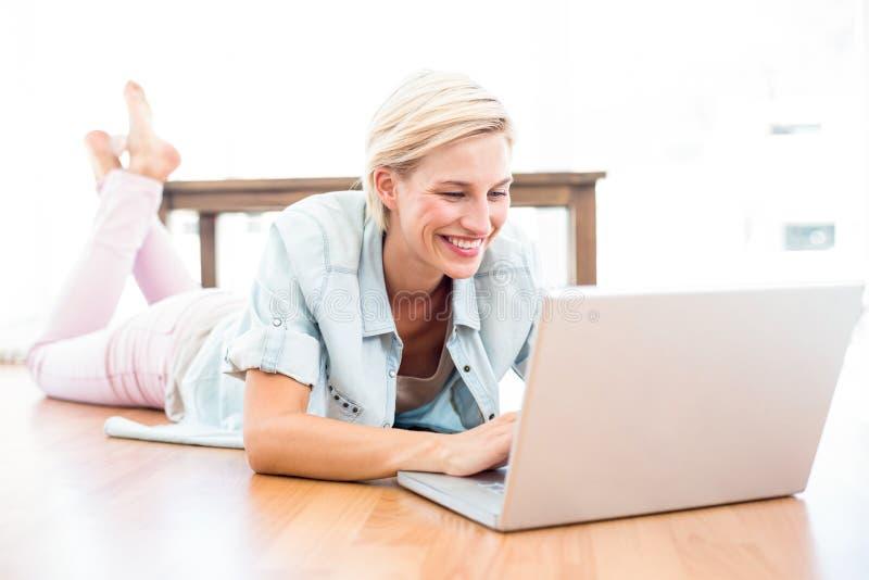 Femme assez blonde se trouvant sur le plancher et à l'aide de son ordinateur portable image libre de droits