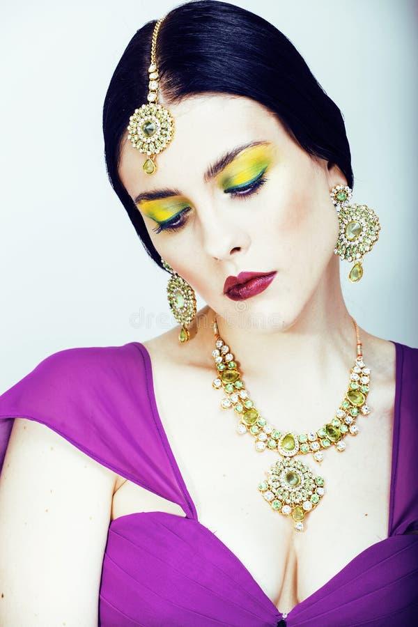 Femme assez caucasienne de jeunes comme l'Indien dans la fin ethnique de bijoux sur le maquillage blanc et nuptiale photos stock