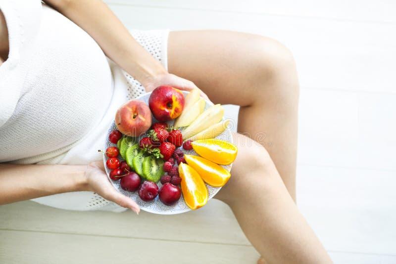 Femme assez enceinte de jeunes avec le plat de fruit photographie stock libre de droits