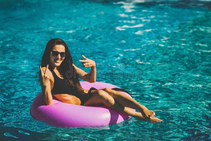 Femme assez heureuse sur l'anneau en caoutchouc dans la piscine images stock