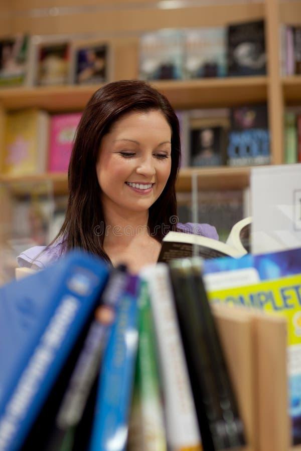 Femme assez jeune affichant un livre photo stock