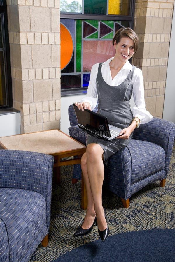 Femme assez jeune avec l'ordinateur portatif dans la salle d'attente photos libres de droits