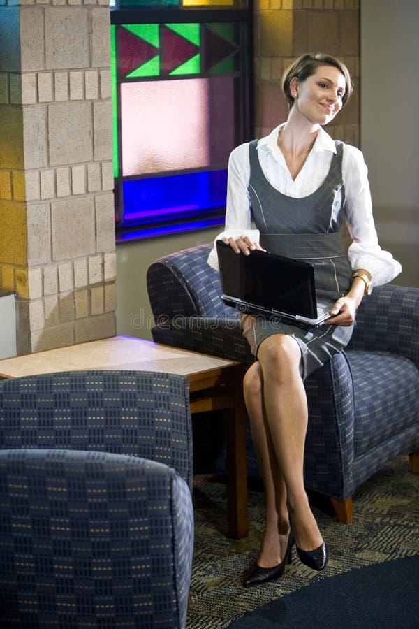 Femme assez jeune avec l'ordinateur portatif dans la salle d'attente images stock