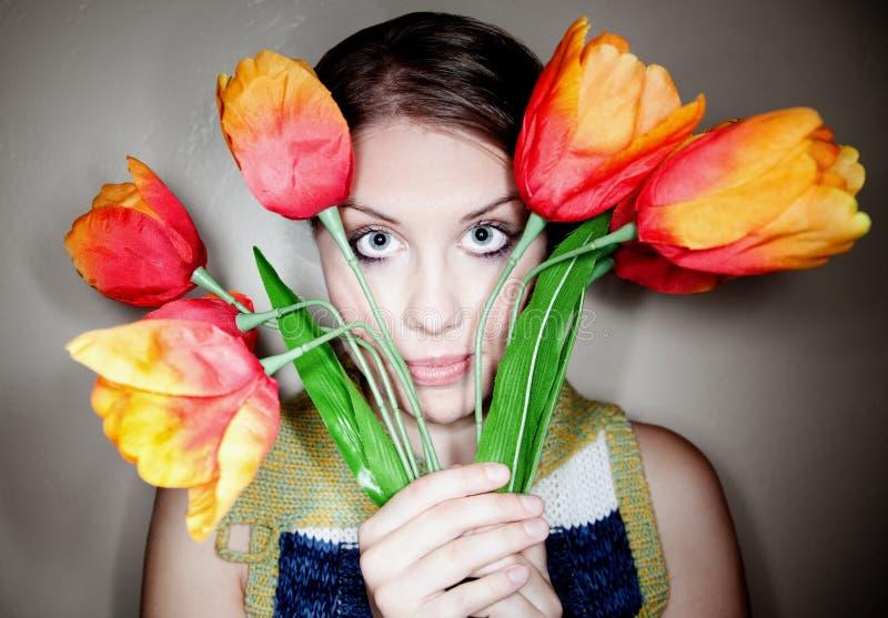 Femme assez jeune avec les fleurs en plastique images stock